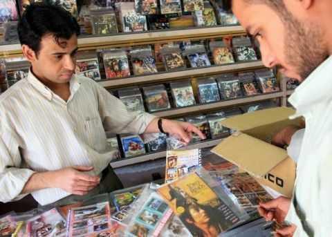 在巴格达市区,一名顾客在音像店挑选盗版光盘。在当地,一张盗版DVD的售价大约是1-1.5美元。