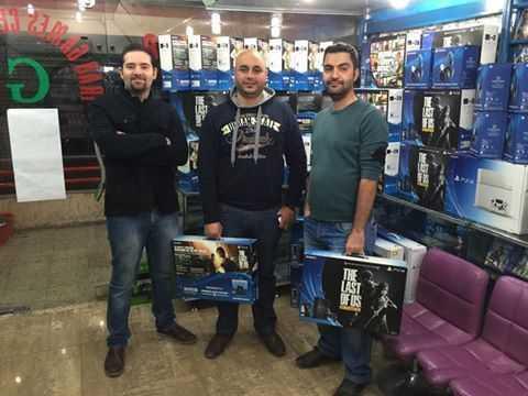 """在""""伊拉克游戏中心"""",两名刚买下《美国末日》同捆版PS4的玩家与店主合影。"""